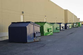 A picture of commercial dumpsters. There are several six to eight yard dumpsters spread out by about ten f0eet each, outside along the wall of a large warehouse.